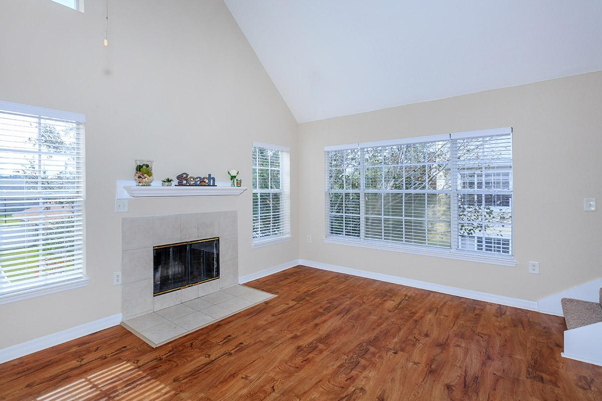 a living room with a wood floor next to a window