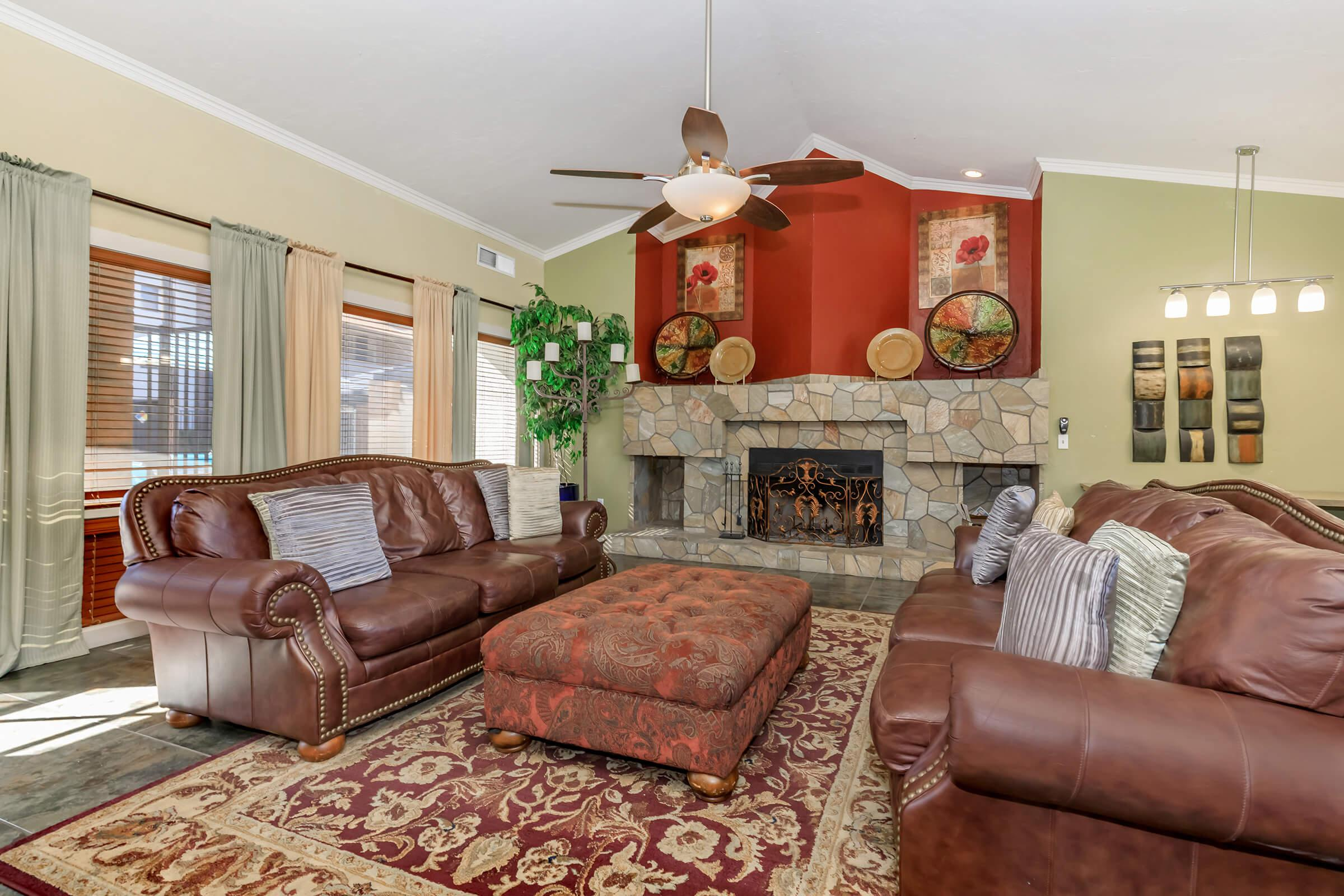 a brown leather couch in a living room filled with furniture and a fireplace
