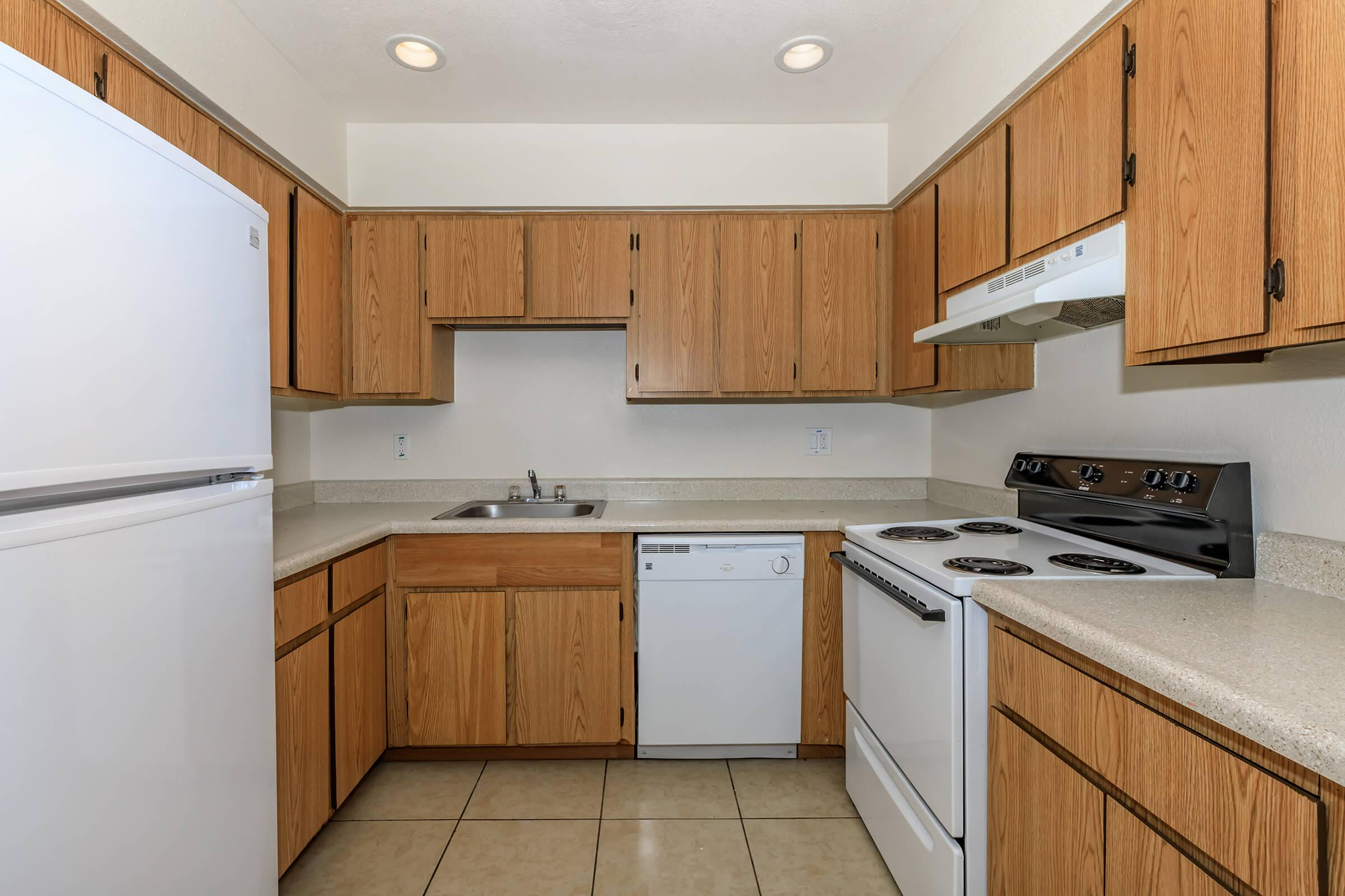 a kitchen with a stove refrigerator and wooden cabinets
