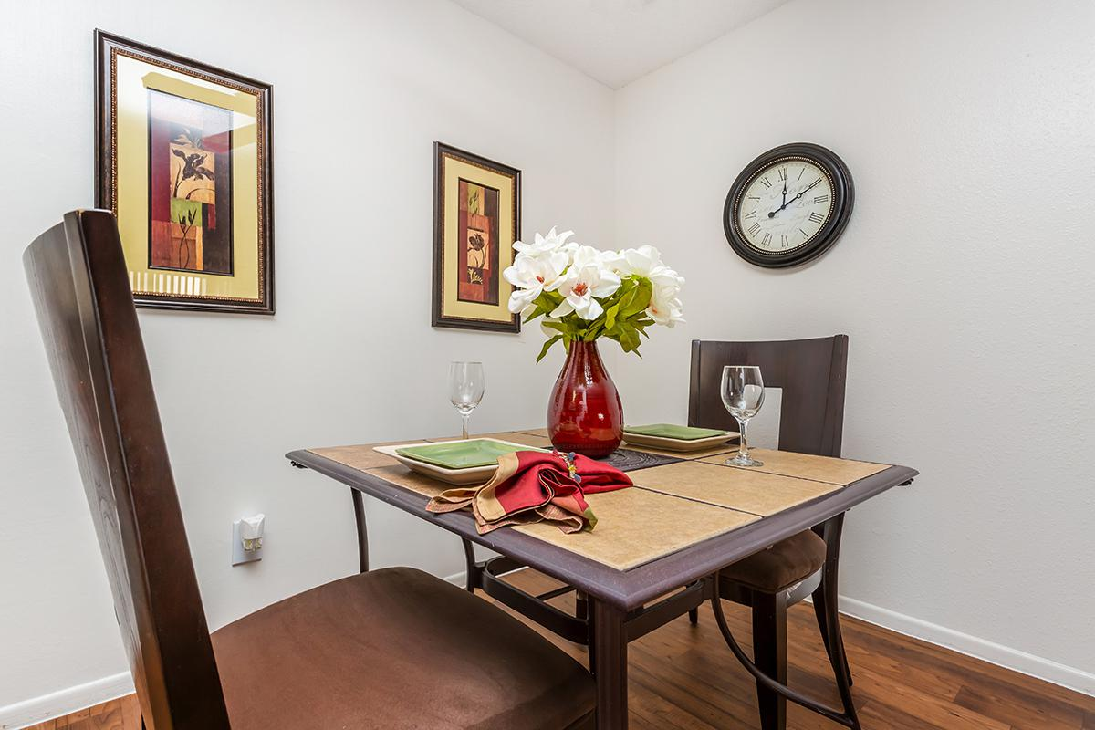 a room that has a clock at the top of a wooden table