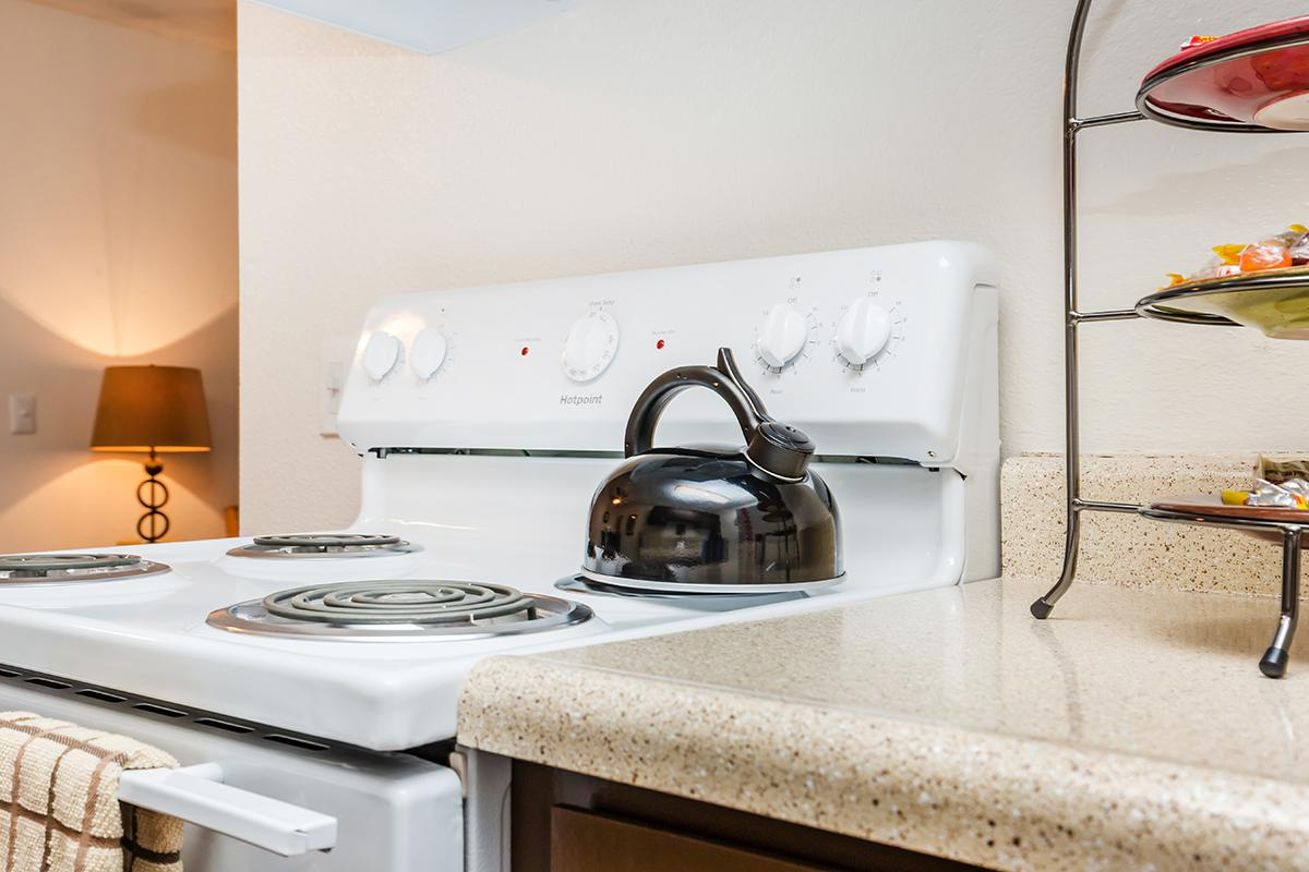 a white stove top oven sitting next to a sink