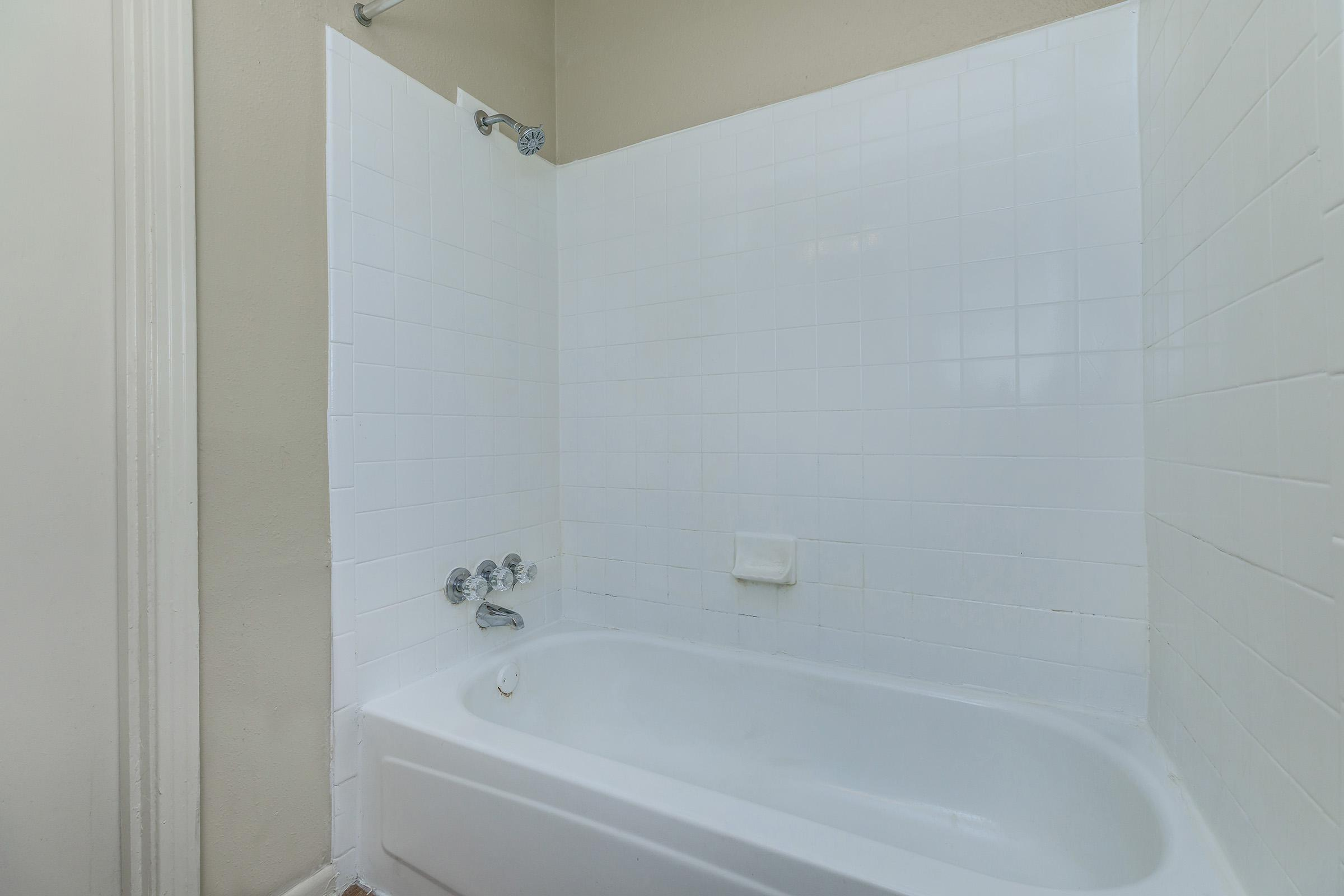 a room with a sink and a white tub sitting next to a shower