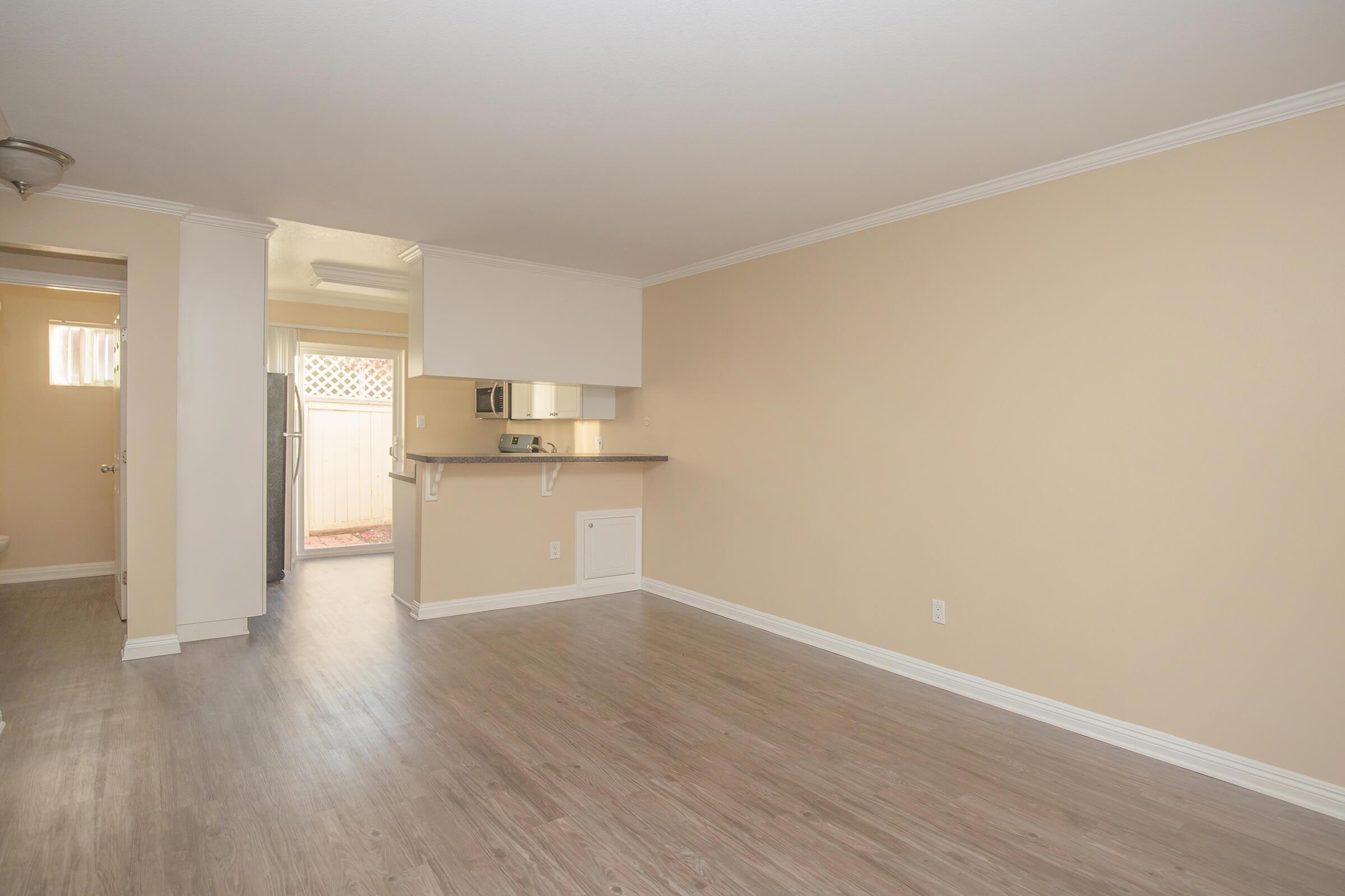 Vacant living room with kitchen in the background