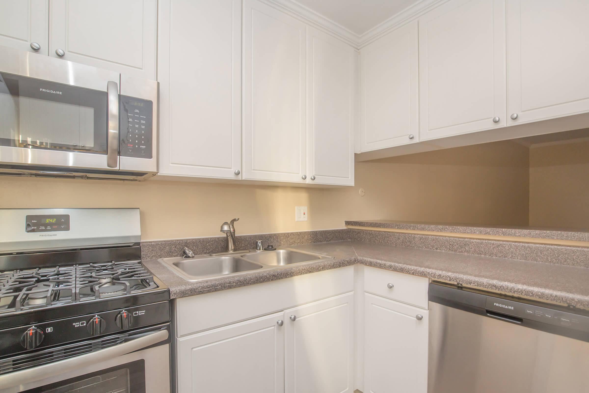 Kitchen with gas stove, dishwasher, microwave, and sink