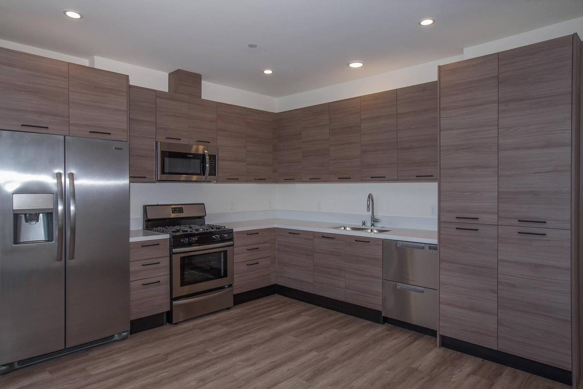 a large kitchen with stainless steel appliances and wooden cabinets