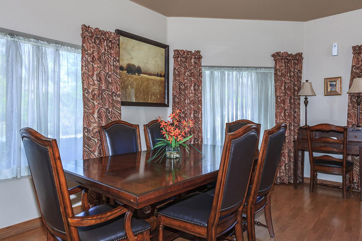 a dining room table in front of a curtain