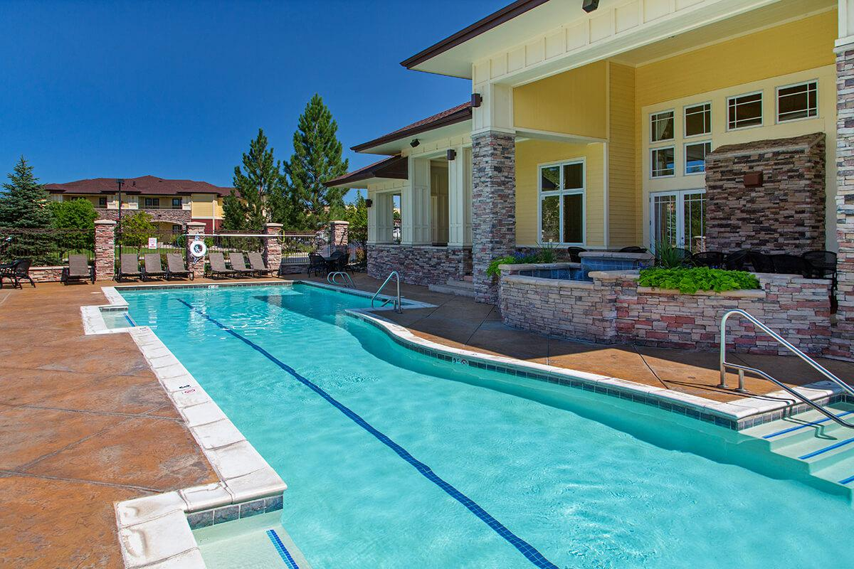 a house with a pool in front of a building