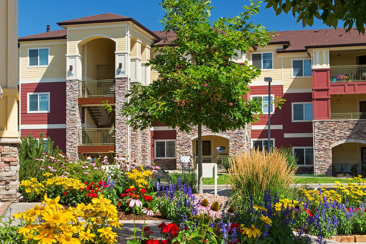 a colorful flower garden in front of a house