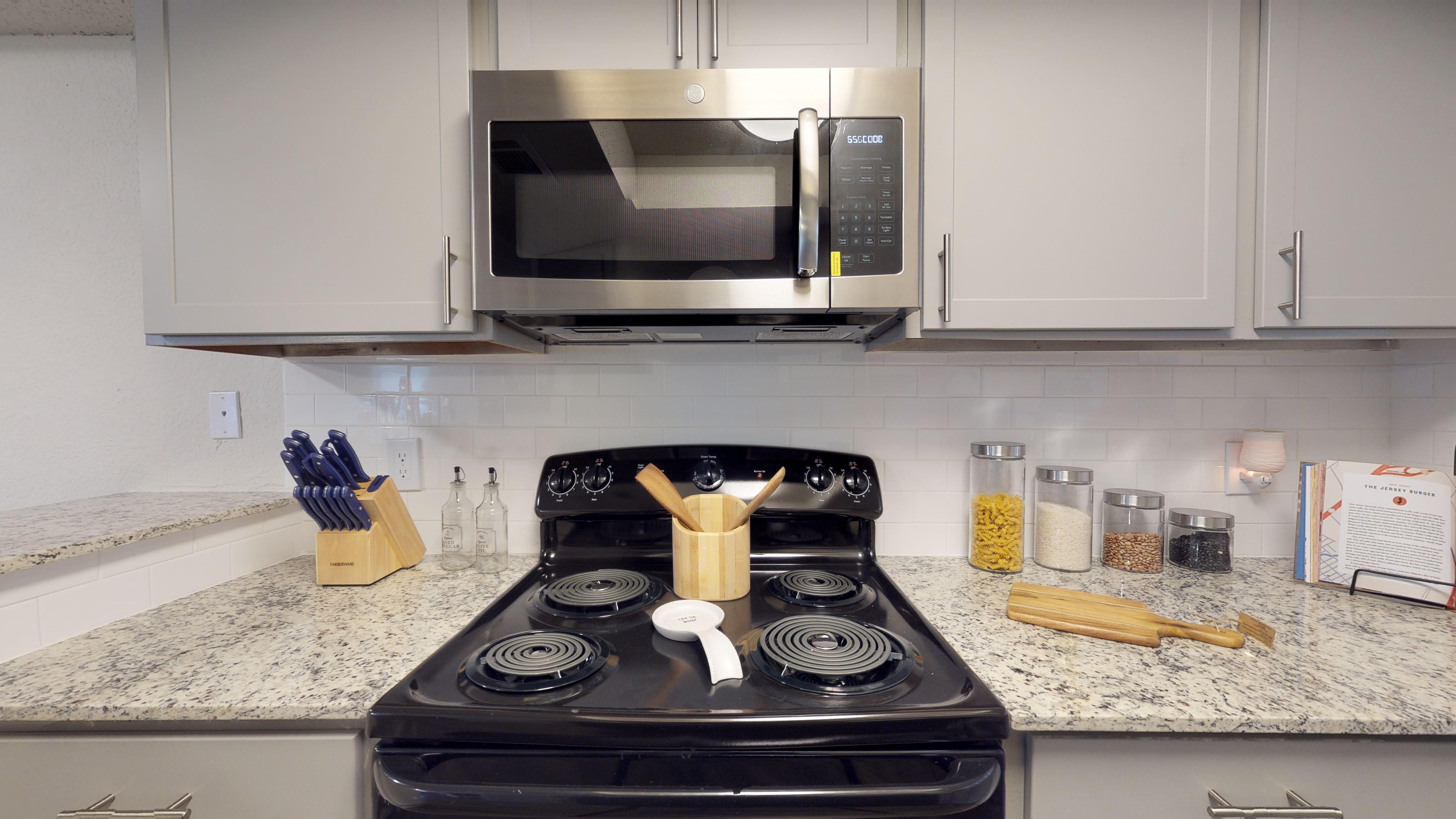 a black stove top oven sitting inside of a kitchen