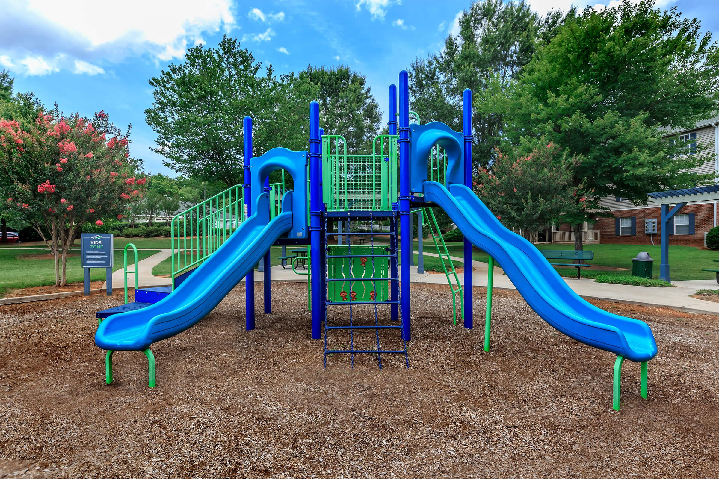 a playground with a blue seat sitting in a chair