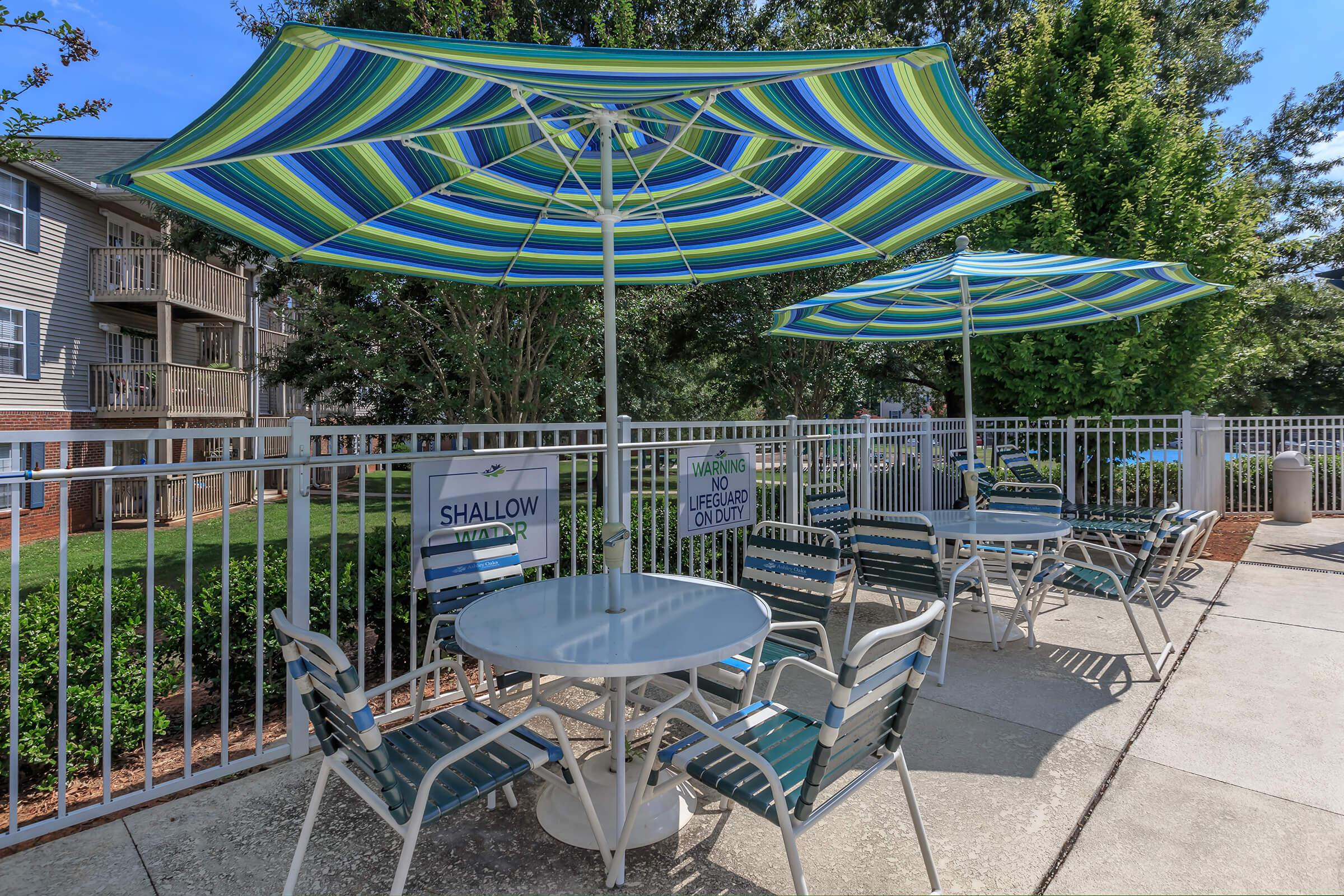 a group of lawn chairs sitting on top of a blue umbrella