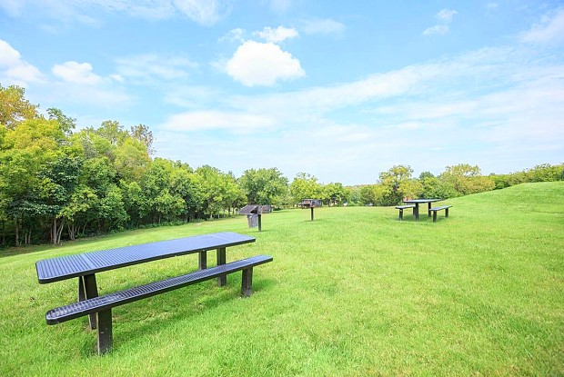 an empty park bench sitting on top of a lush green field