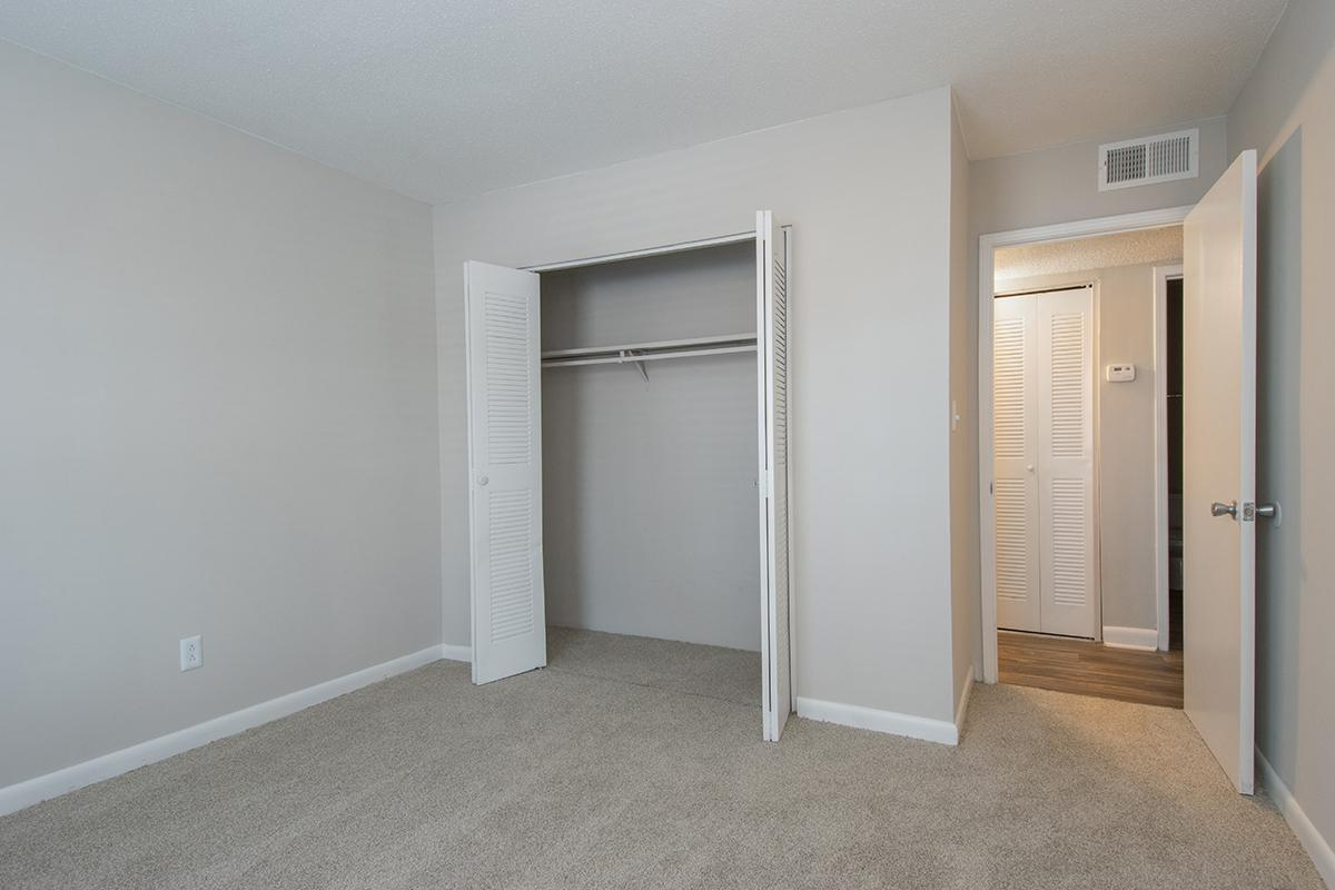 a large empty room with a sink and a mirror