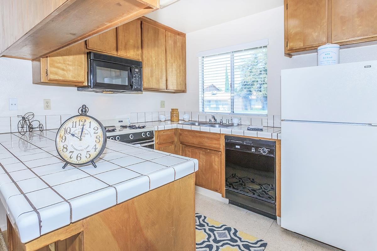 a kitchen with a clock at the top of a refrigerator