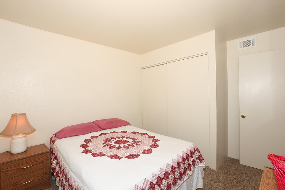 a bedroom with a neatly made bed with a red blanket