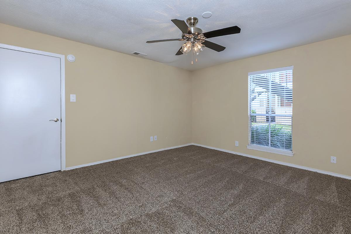 a bedroom with a ceiling fan in a room