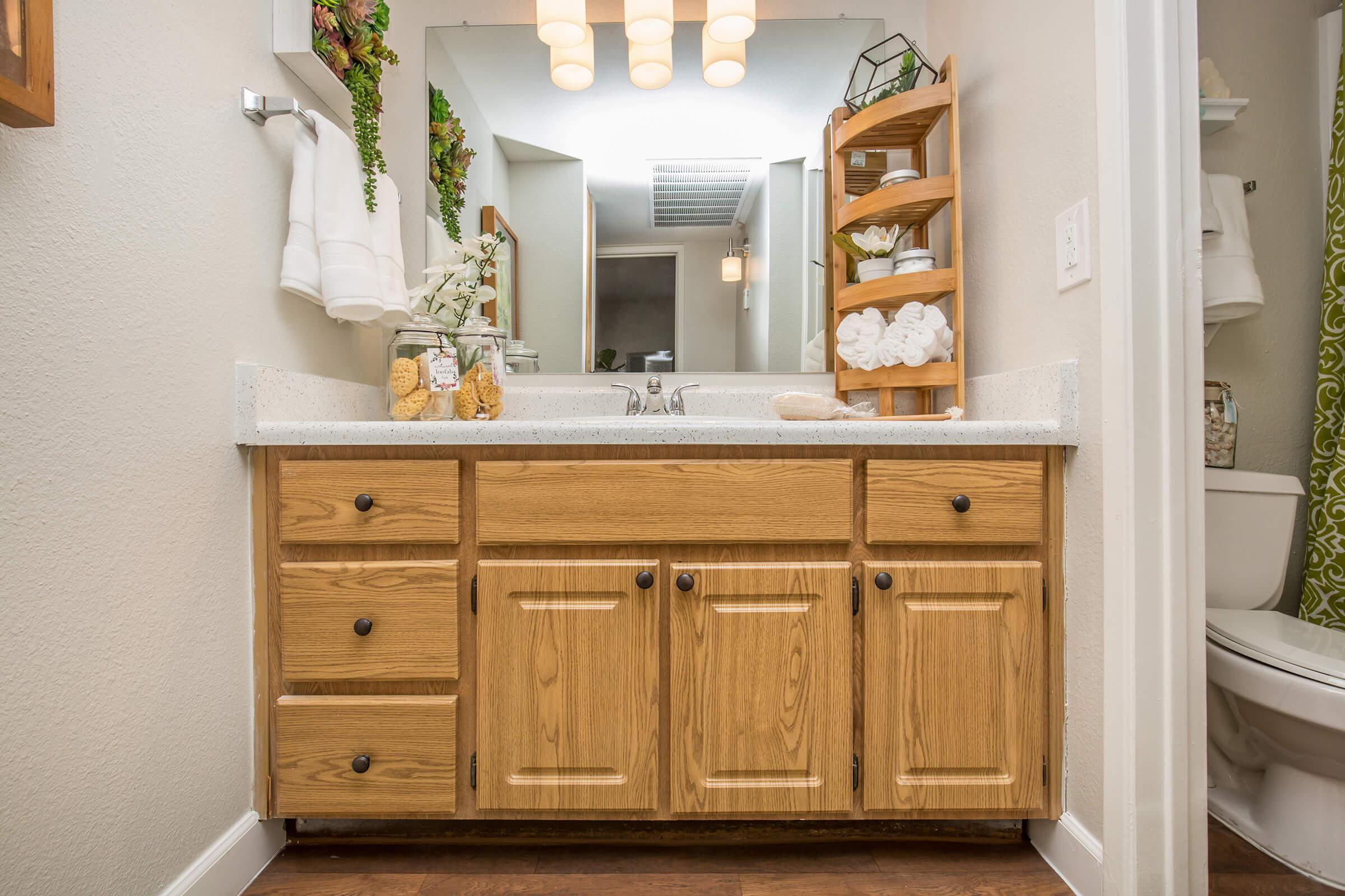 a kitchen with wooden cabinets and a mirror