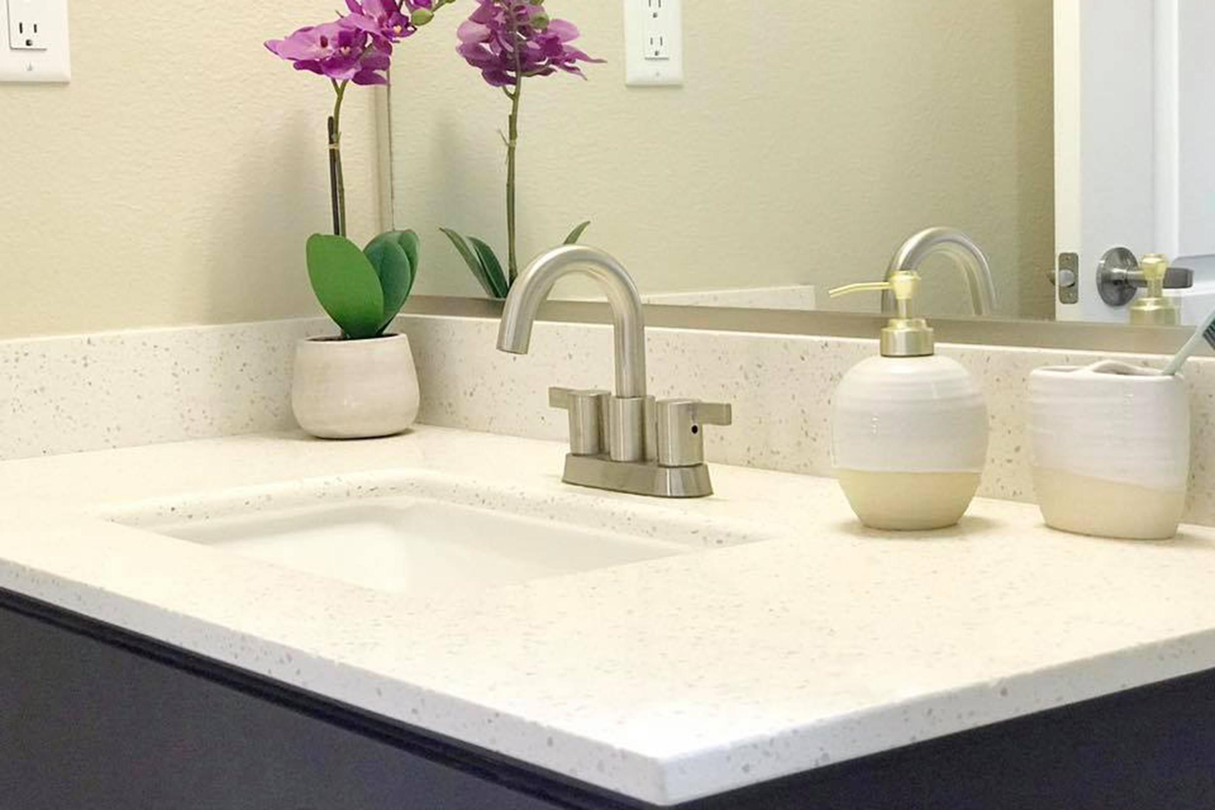 a white sink sitting next to a vase of flowers on a table