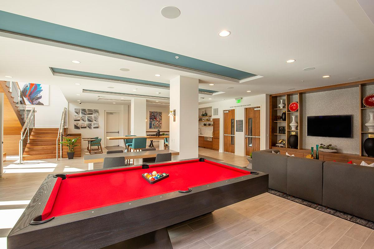 Community room filled with furniture and a red pool table