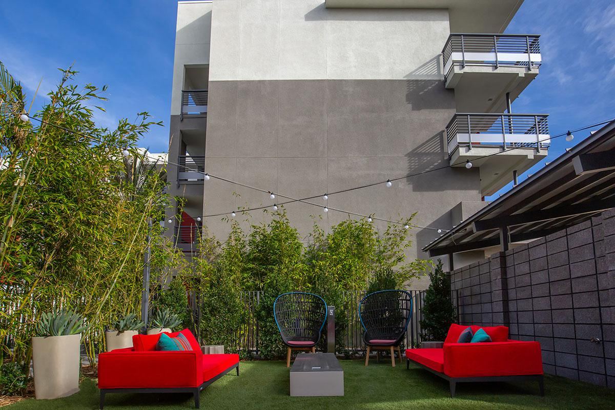 Red couches and table on Calligraphy Urban Residences rooftop
