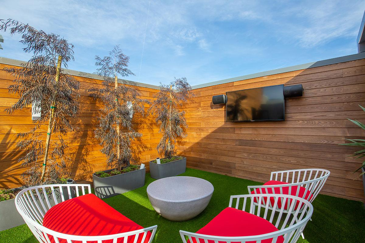 Red chairs with a TV on Calligraphy Urban Residences rooftop