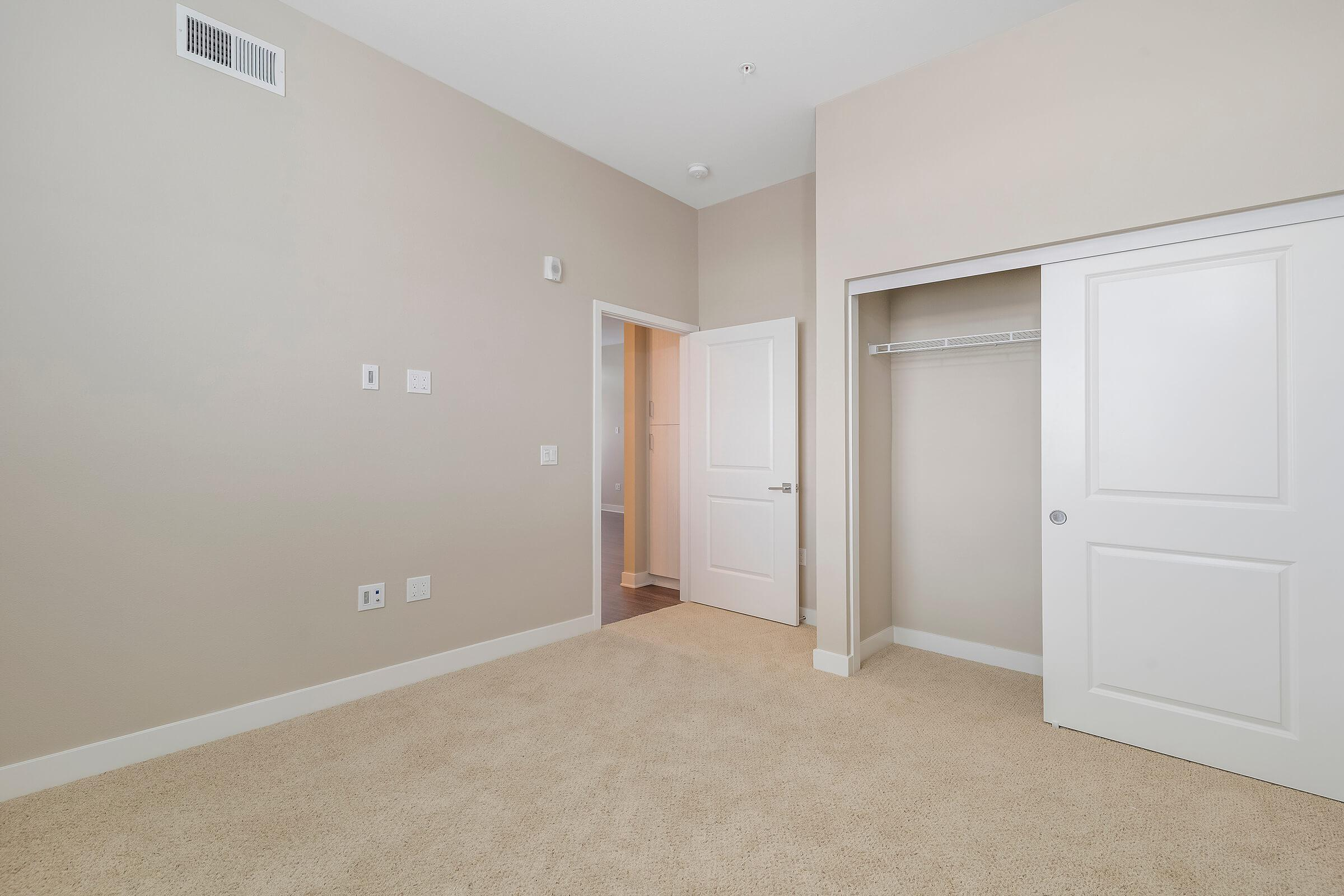 Carpeted bedroom with open sliding closet doors