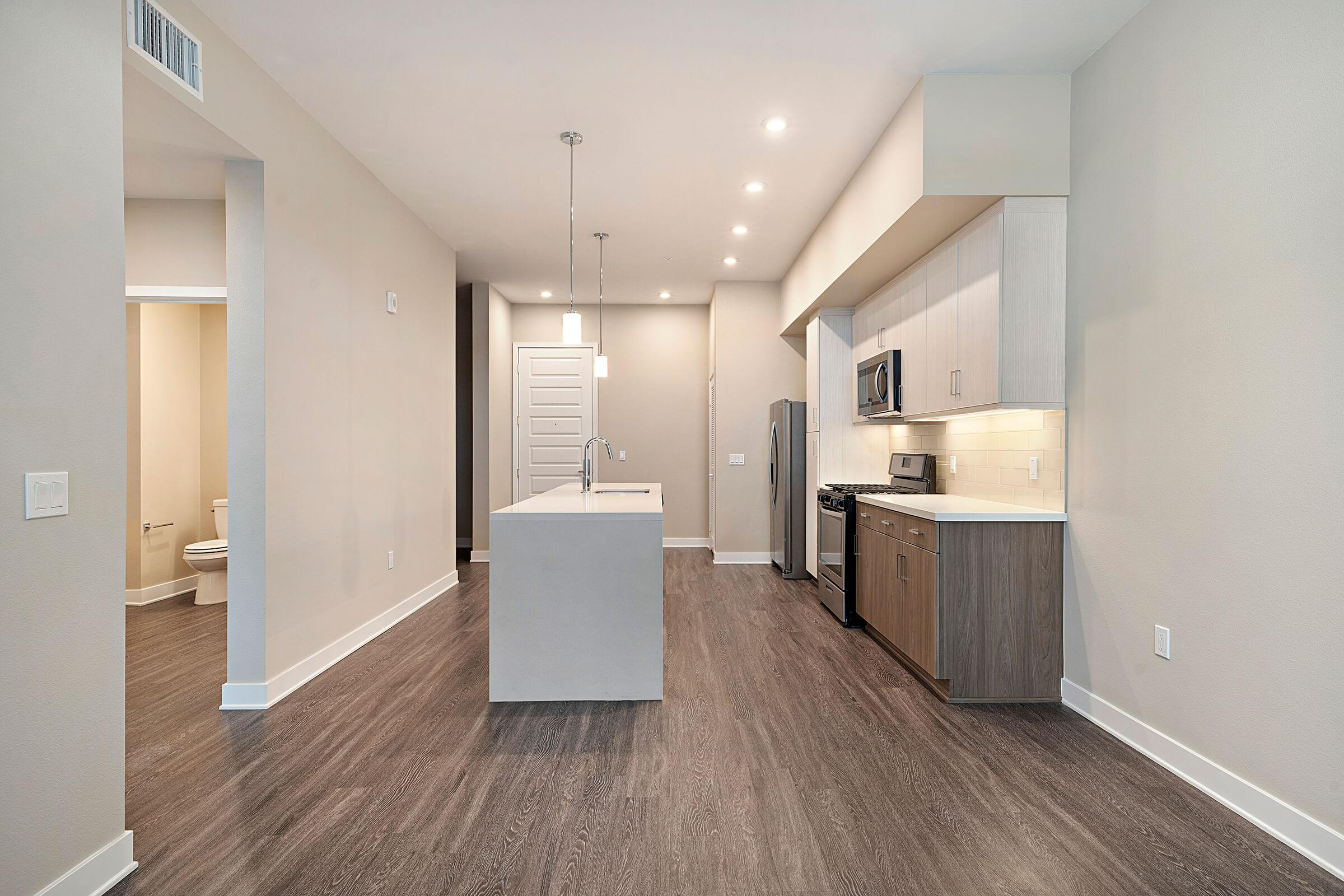 Unfurnished dining room and kitchen with wooden floors