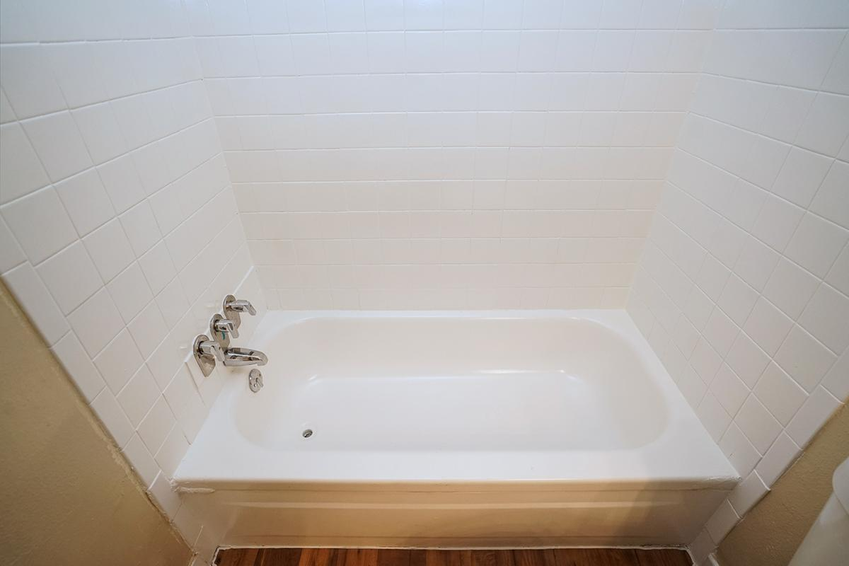 a white tub sitting next to a tiled wall
