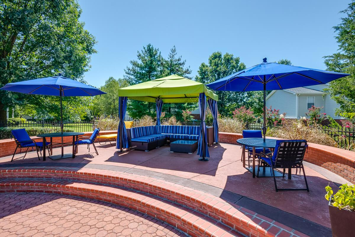 a group of lawn chairs sitting on a table with a blue umbrella