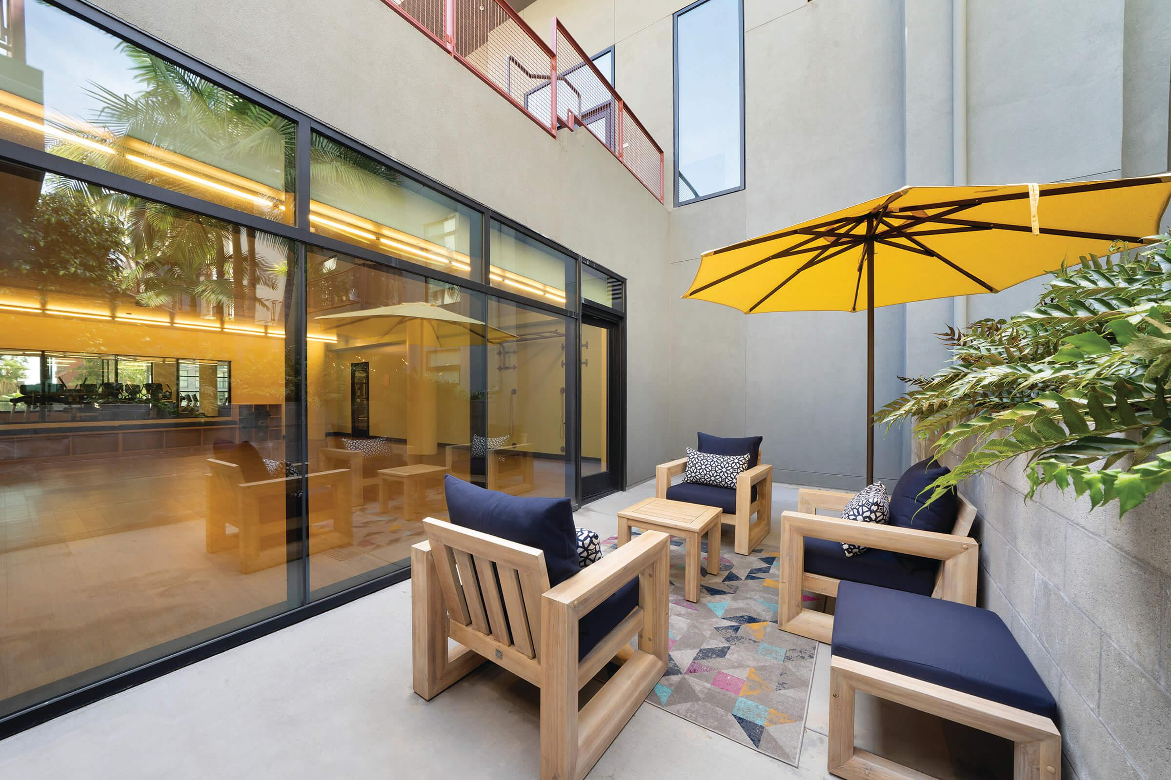 Community patio with couches and yellow umbrella