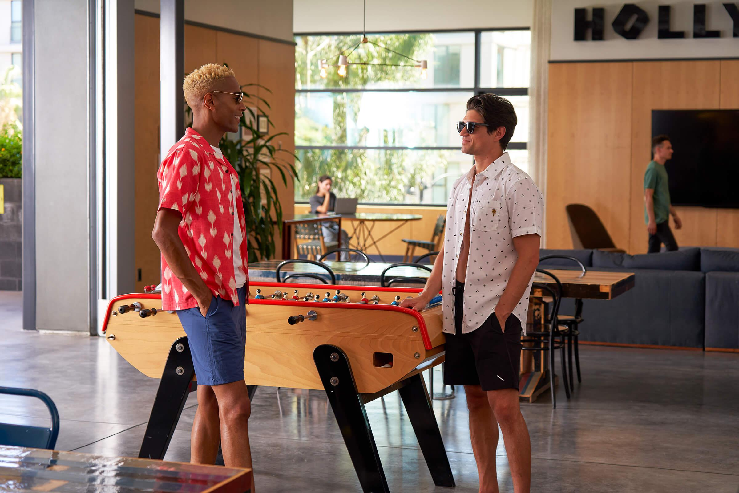 Two people standing in front of foosball table