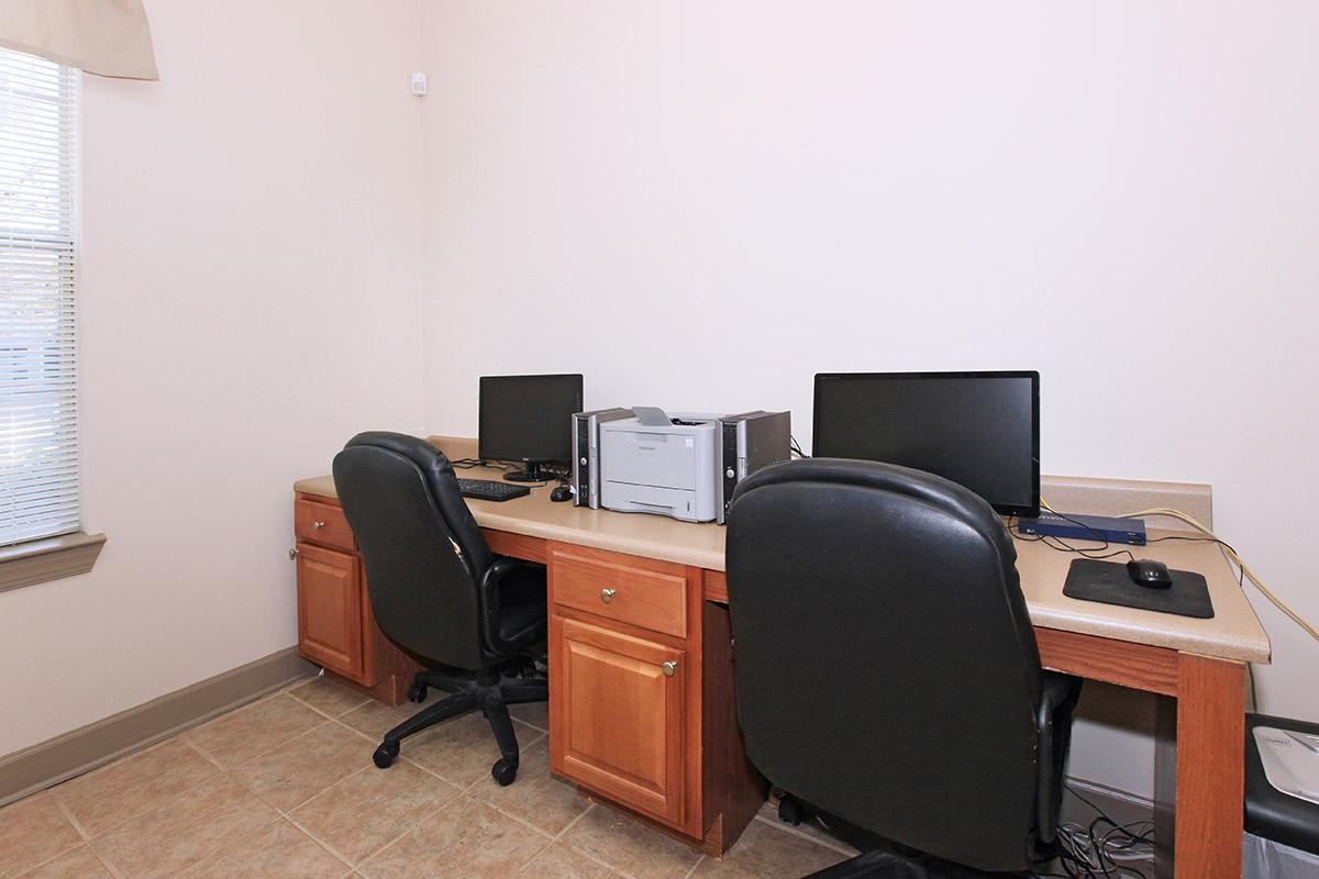 a desk with a computer in an office chair in a room