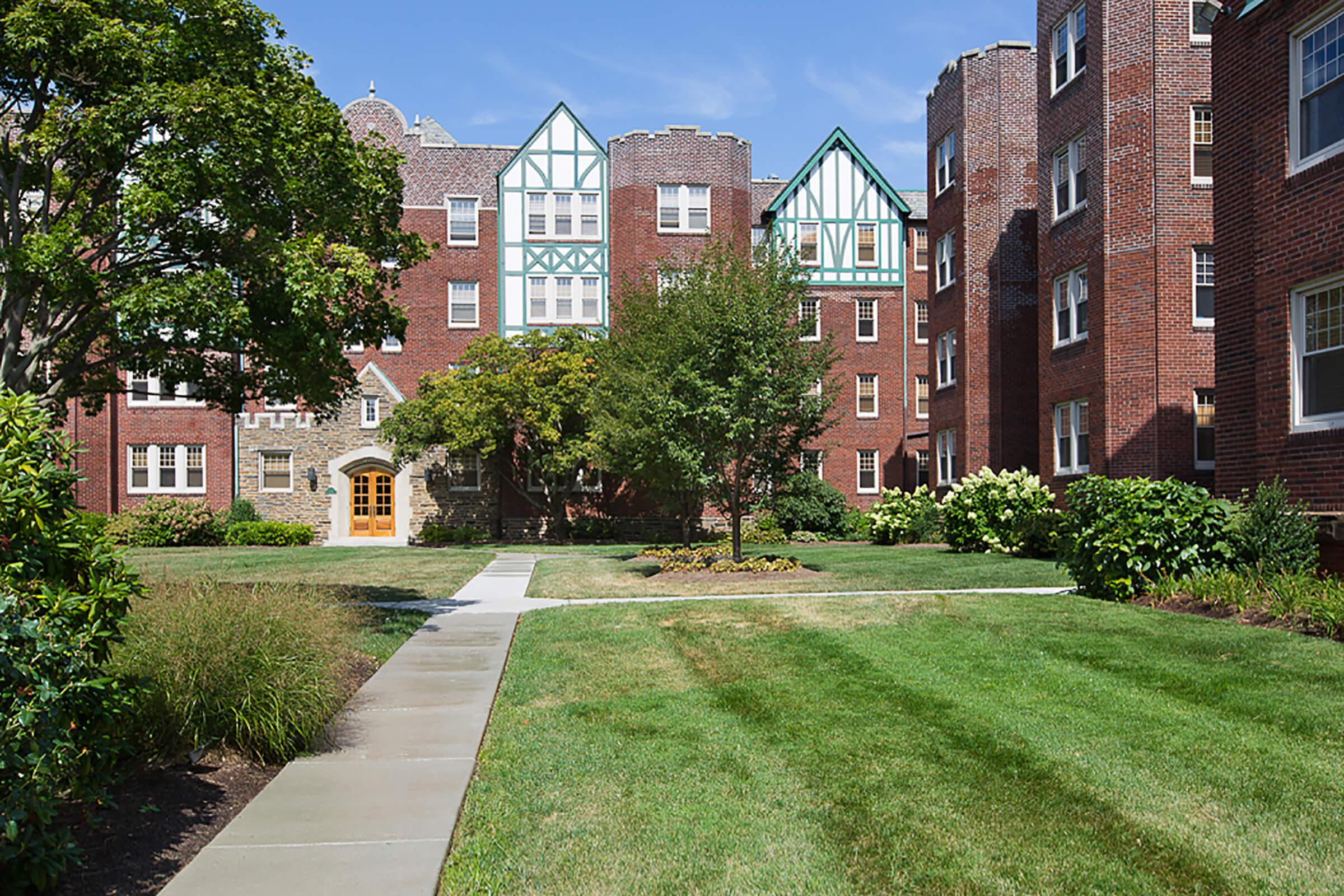 a path with grass in front of a brick building