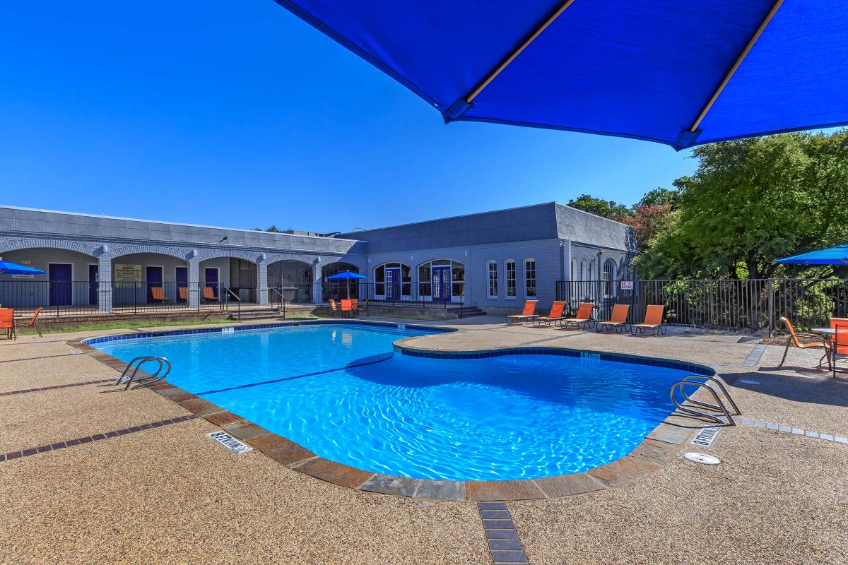 a blue umbrella sitting next to a swimming pool
