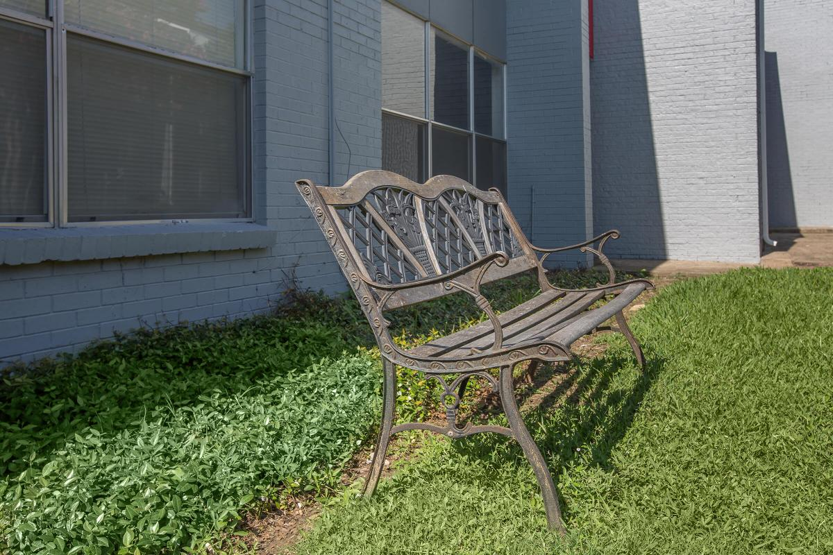 a couple of lawn chairs sitting on a bench in front of a building