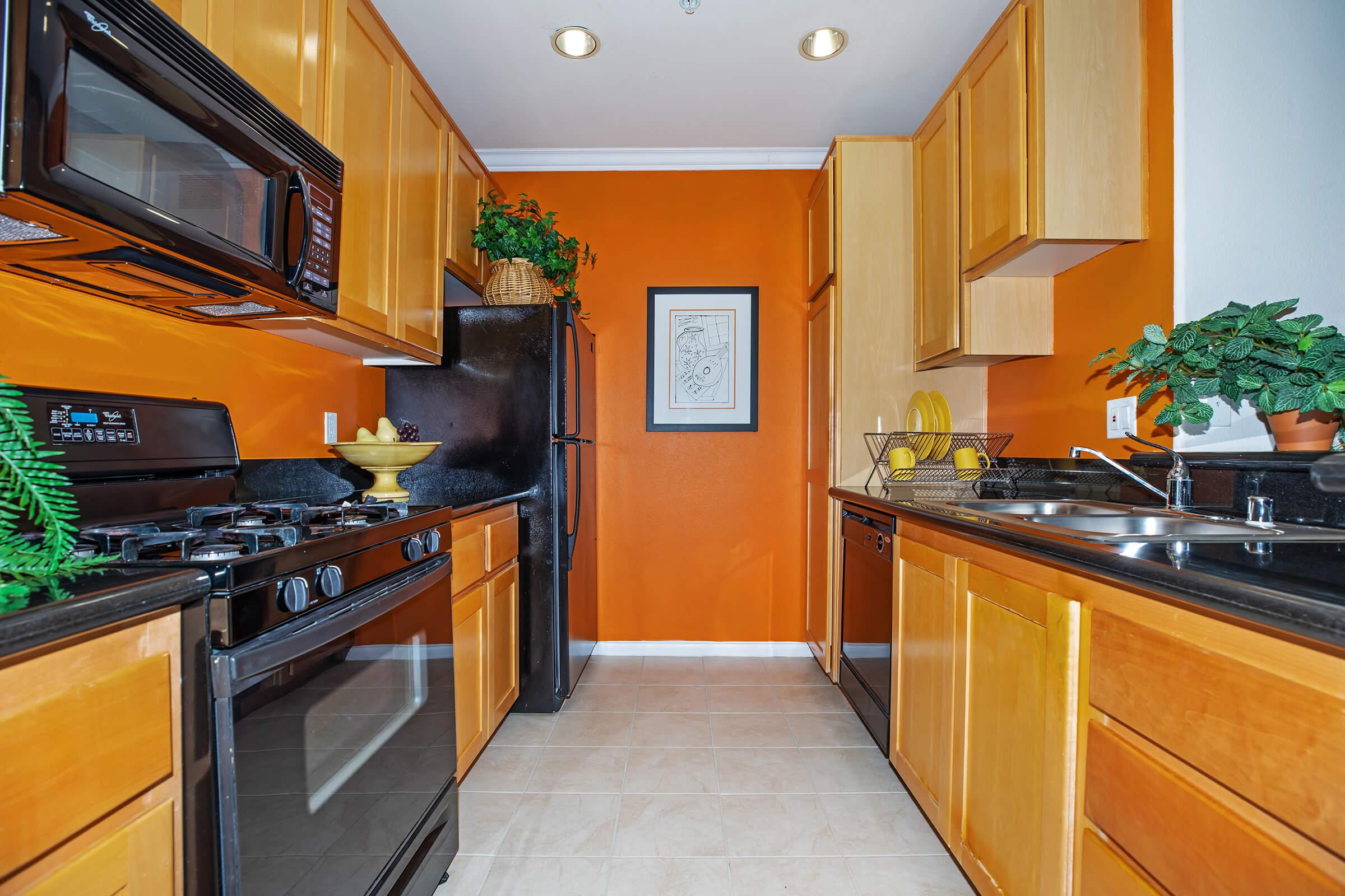 a yellow kitchen with black counter tops