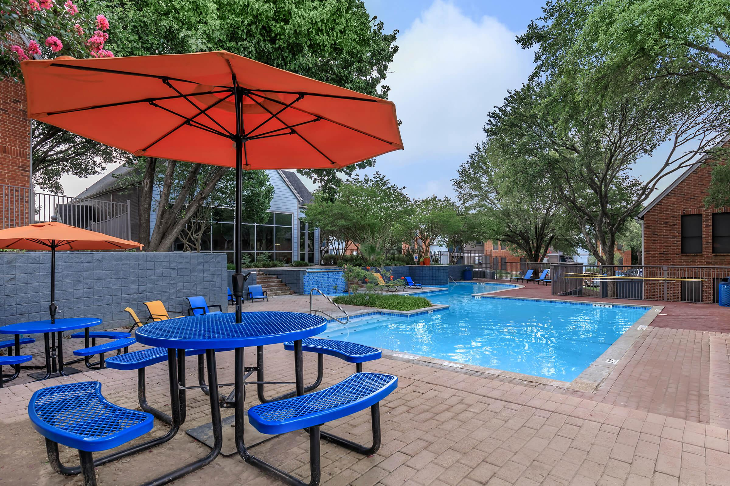 a row of lawn chairs sitting on a pool table with a blue umbrella