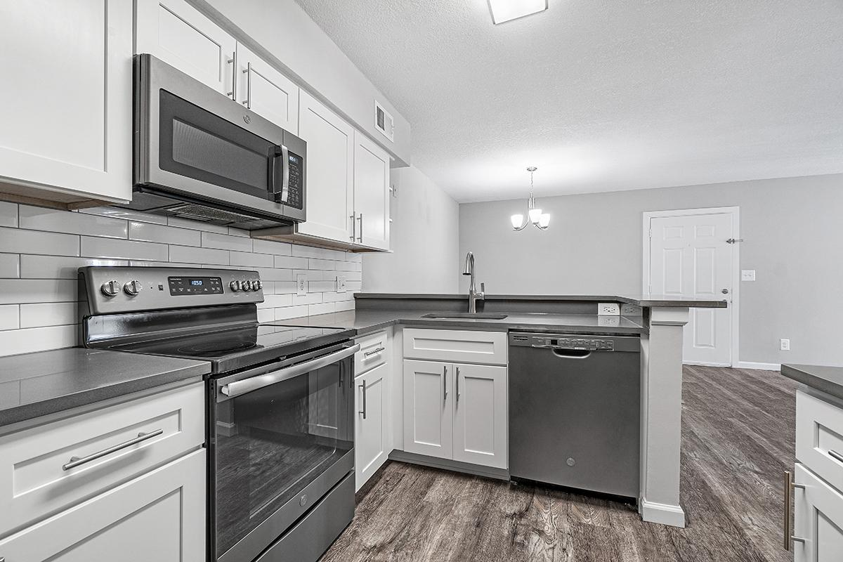 a kitchen with white cabinets and a black stove