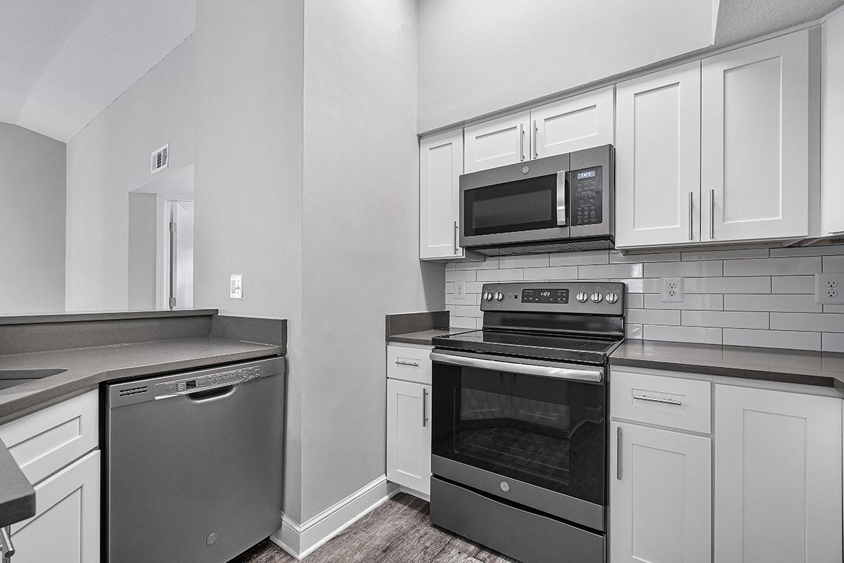 a kitchen with white cabinets and black appliances