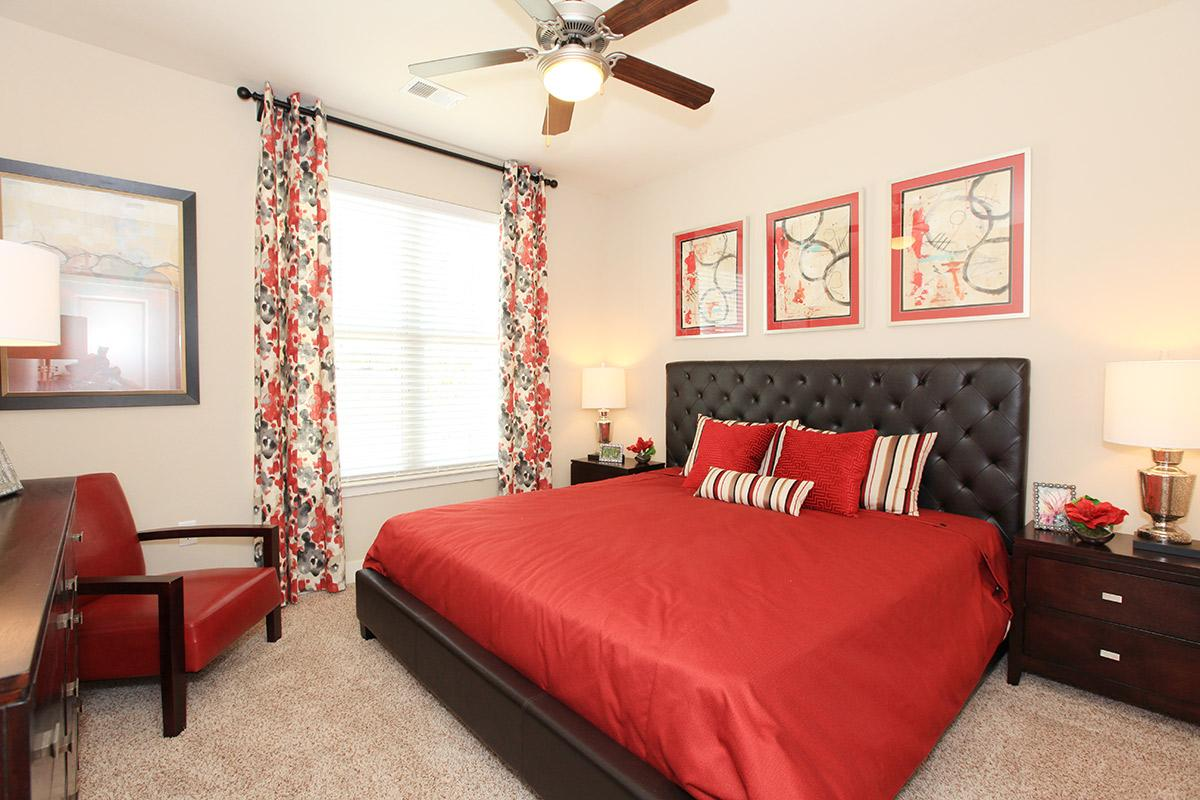 a bedroom with a large red chair in a room