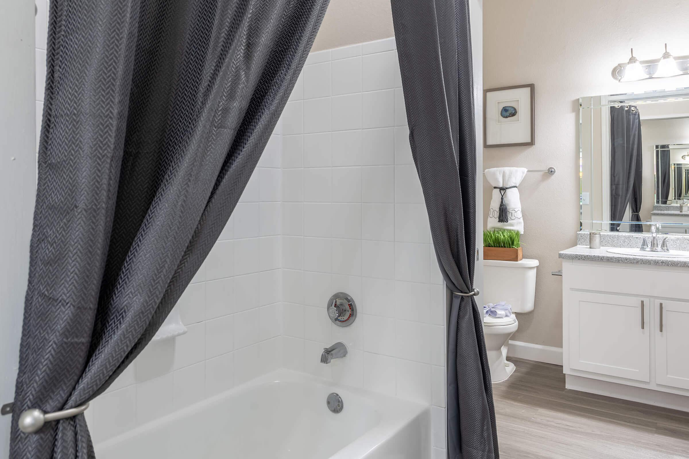 a shower curtain with a white tub sitting next to a sink