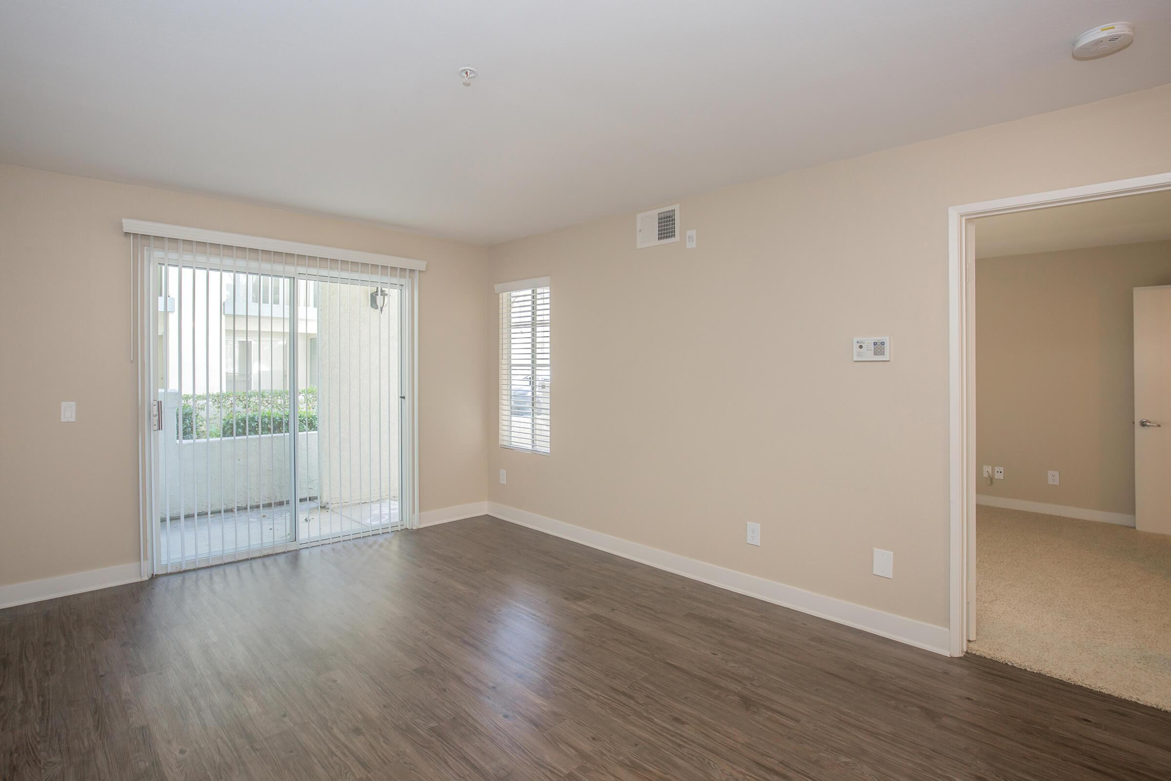 Vacant living room with glass sliding doors to patio