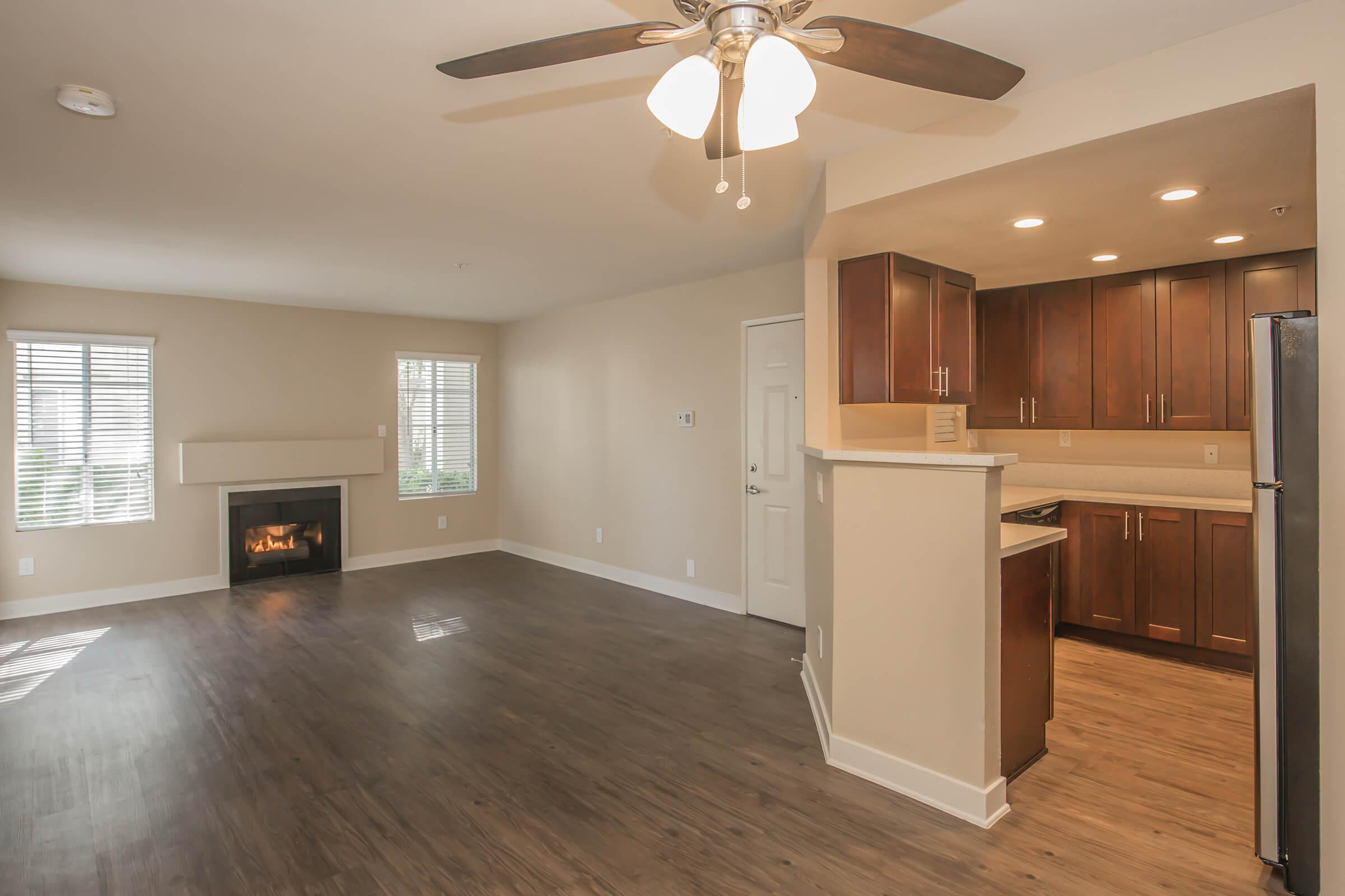 Unfurnished living room with fireplace and kitchen