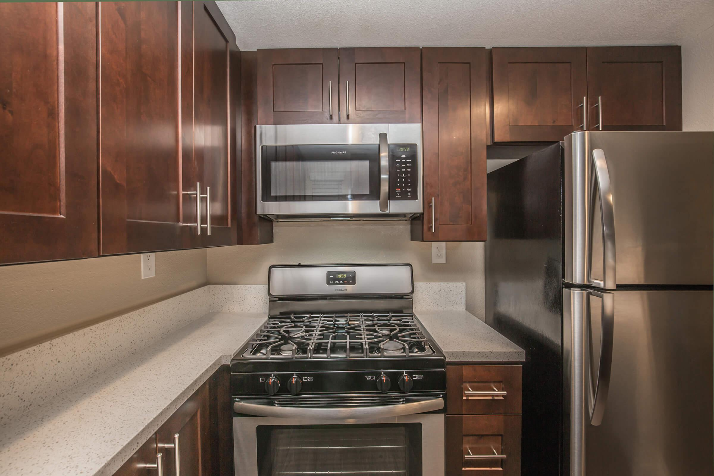 a stove top oven sitting inside of a kitchen with stainless steel appliances and wooden cabinets