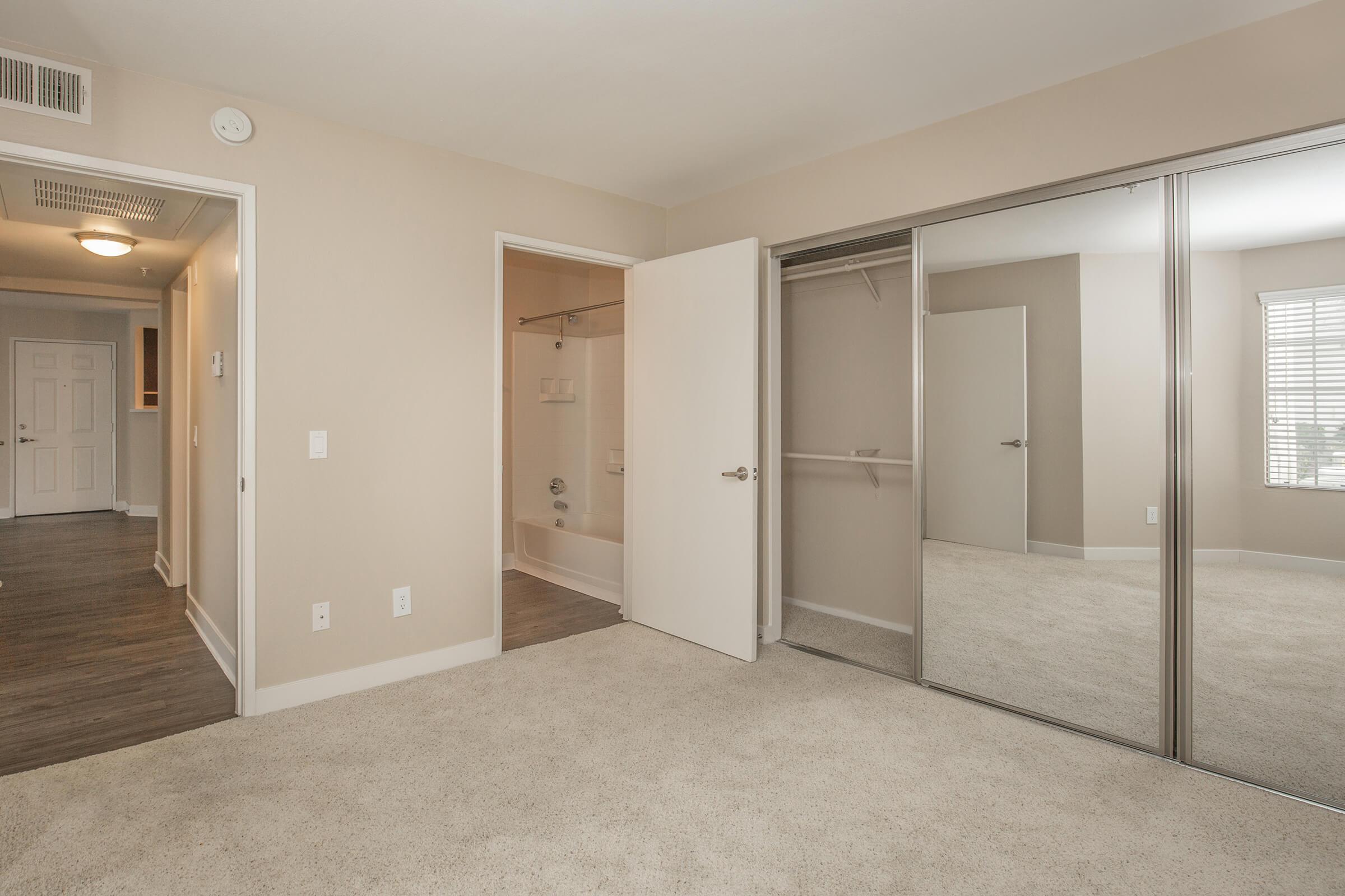 Unfurnished bedroom with mirror sliding closet doors