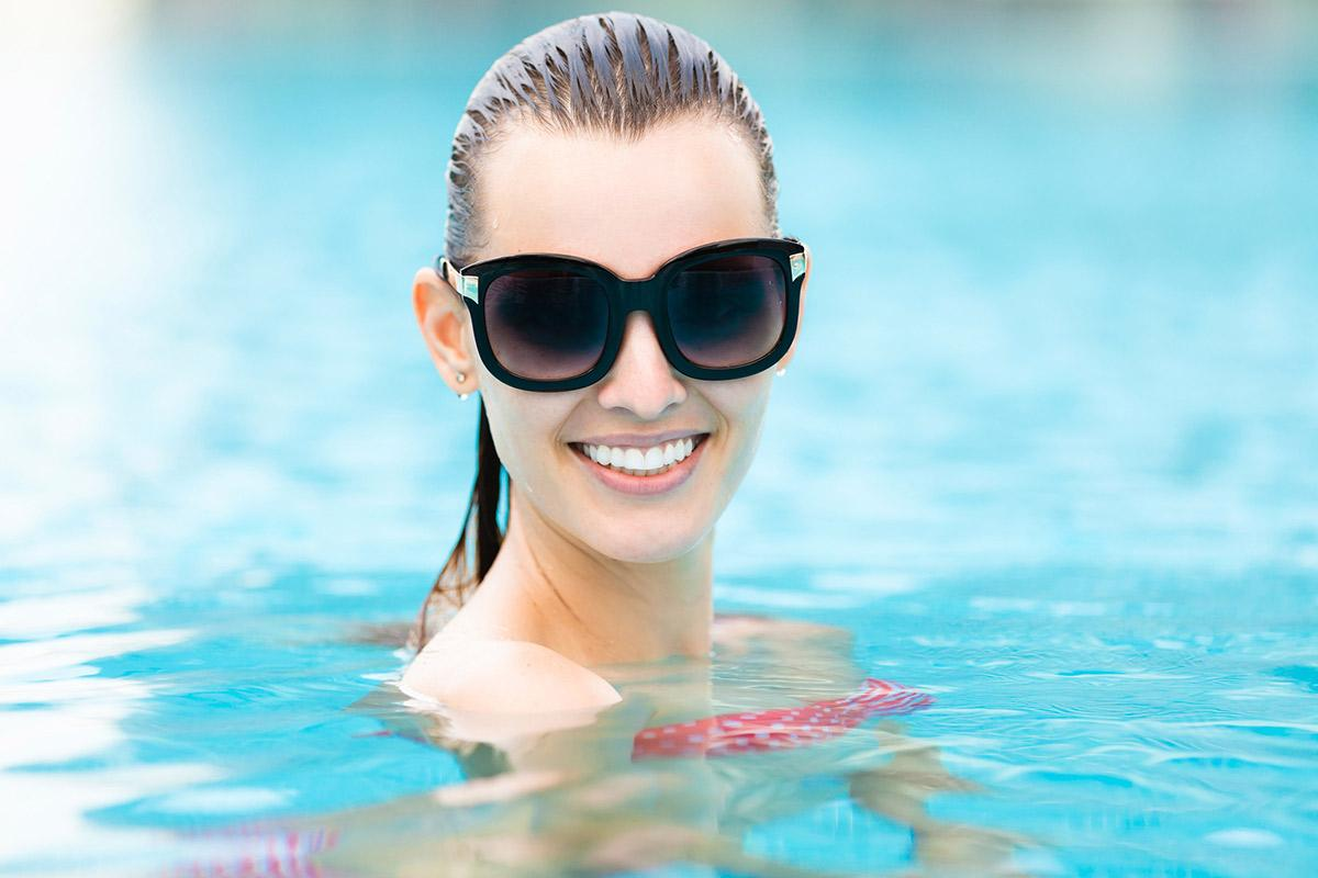a person swimming in the water wearing sunglasses