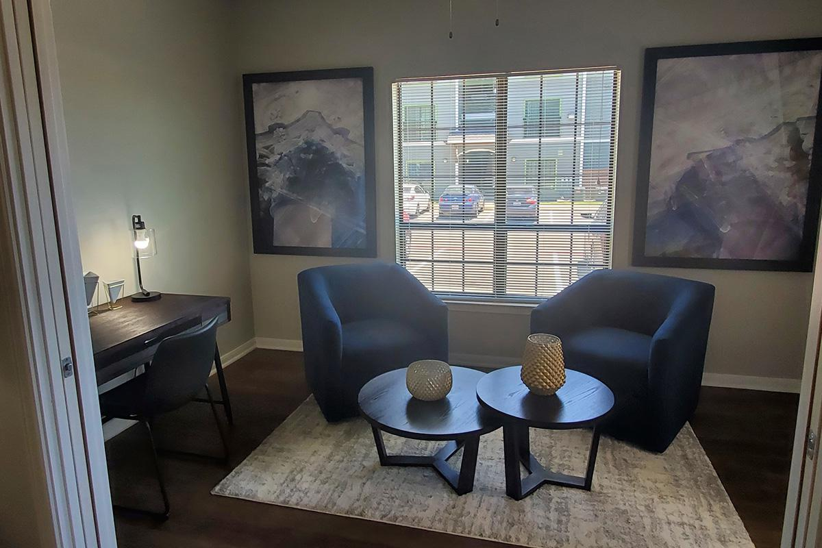 a living room with a couch and a chair in front of a window