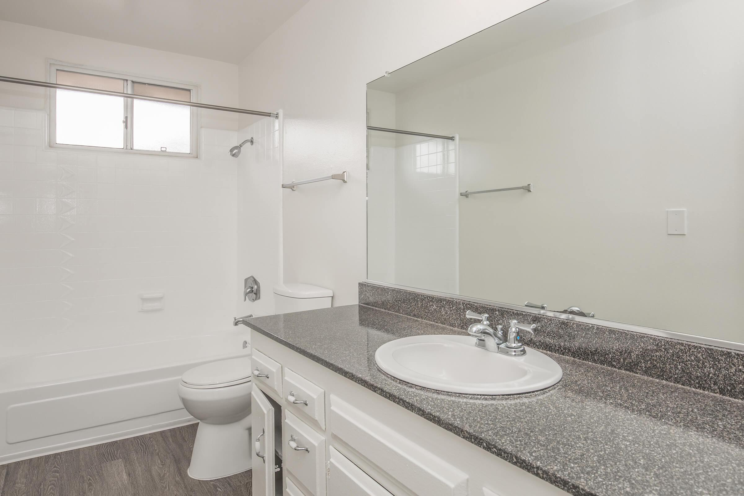 Bathroom with white cabinets and mirror