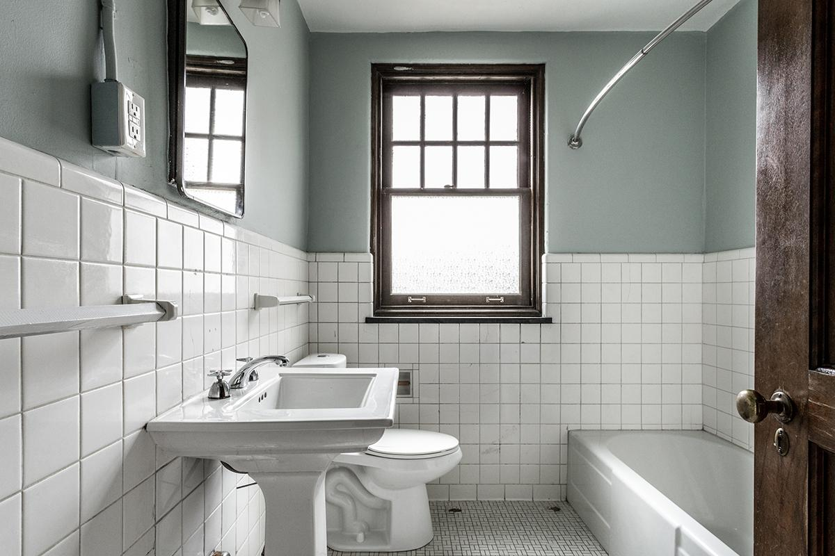 a restroom with a sink and a window
