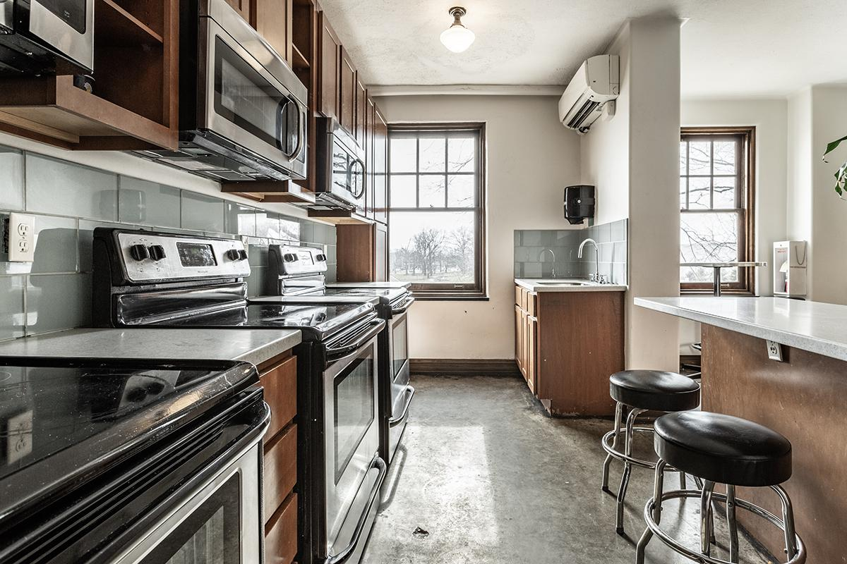 a kitchen with a stove top oven sitting next to a window